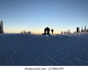 Profiles of snowboarders and skiiers watching sunset
