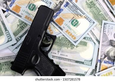 profit from criminal activity. proceeds of crime. black metal pistol, gun on a pile of american 100 dollar bills