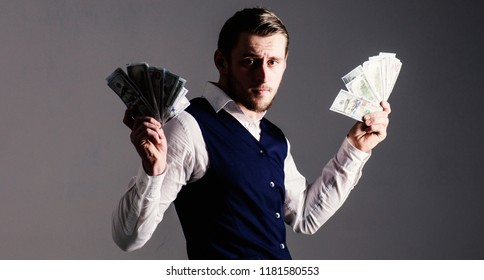 Profit and richness concept. Man in waistcoat, businessman, entrepreneur holding lot of money in both hands, grey background. Rich man, successful entrepreneur get cash, banknotes, currency, dollars.