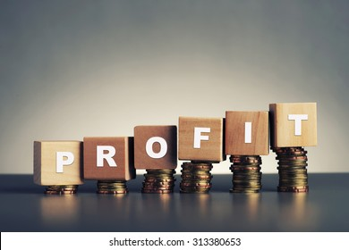 profit text written on wooden block with stacked coins on grey background