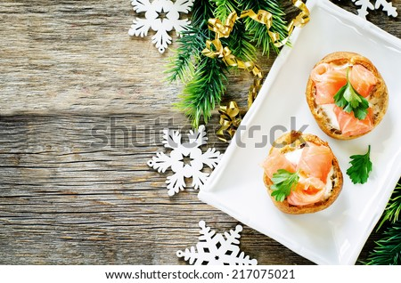 profiteroles with salmon and cream cheese on a dark wood background. tinting. selective focus on parsley on the top profiterole