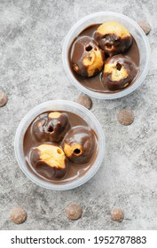 Profiteroles served in tubs with chocolate sauce