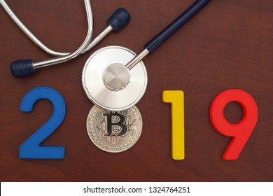 Prognosis bitcoins cost concept and cryptocurrency future for year 2019. Stethoscope and bitcoin coin with numbers 2019.