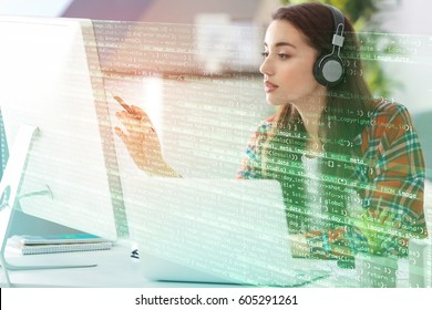 Program development concept. Young woman listening to music while working with computer