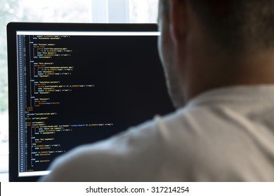 programmer from behind and programming code on computer monitor. focus on monitor