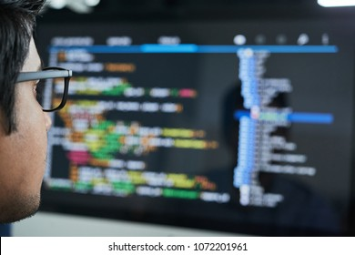 Programmer checking code on computer screen, selective focus
