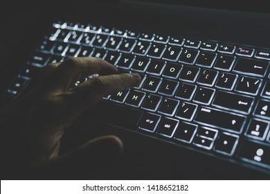 Programmer or computer hacker typing code on laptop keyboard. The keypad is lit in white light. hand presses a key on your computer