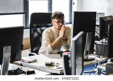 Programmer sitting at the desk in his office and trying to solve problem of new code.