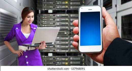 Programmer and smart phone in server room