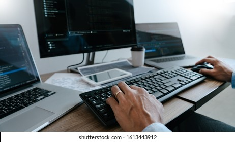 Programmer working On Computer In IT Office Typing Data Coding in software and checking code on computer screen