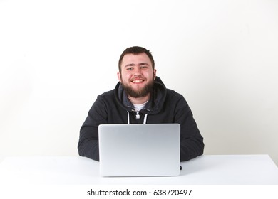 The programmer works behind the laptop. Isolated, one person on a white background. Horizontal. He is calm.