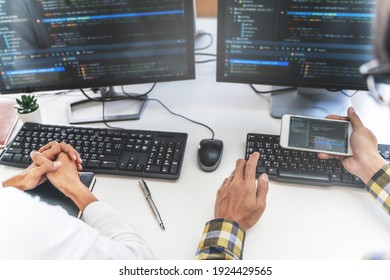programmer writing program code with two monitors and working on new software or hacker programming developing software applicationsin the office.