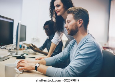 Programmers cooperating at  IT company developing apps - Shutterstock ID 602579849