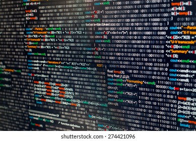 Programming abstract - source code and binary code on display of software developer. Black theme with colored syntax.