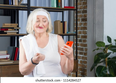 Progressive modern granny concept. Elderly woman blogger measures pulse by phone wearing white sport suit headband and black fitness tracker with white towel holding smartphone in room with bookshelf