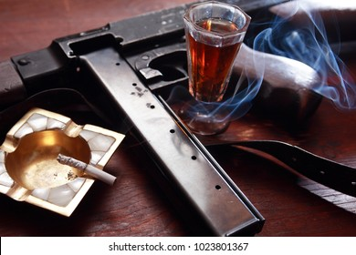 Prohabitation concept. Old USA submachine gun near drink and cigarette