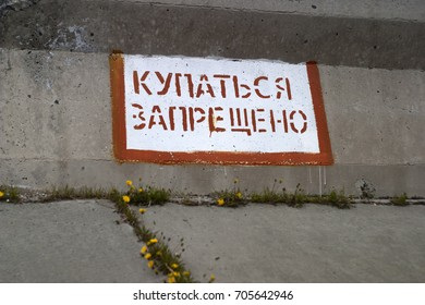 "Prohibiting sign, carefully, dangerously, in Russian: ""Bathe forbidden"". Red font on white background. Concrete fencing"