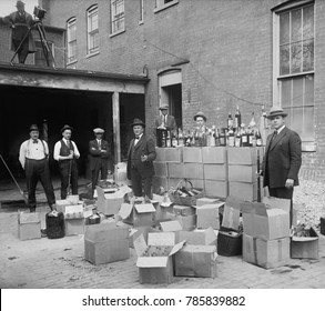 Prohibition agents stand with boxes and bottles of wine and liquor after a raid in Wash. D.C. area. Oct. 14, 1922. Note the camera man in upper left