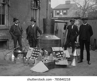 Prohibition agents stand with a still and mason jars used to distill hard liquor in Wash. D.C. area. Nov. 11, 1922