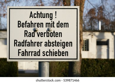 Prohibition sign for cyclists on a footpath with the inscription driving with the wheel forbidden, bicyclists descend, push bicycles