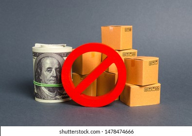 The prohibition sign NO blocks a bundle of dollars money and cardboard boxes. Embargo, trade wars. Restriction on importation goods, proprietary for business. Sanctions and economic restrictions