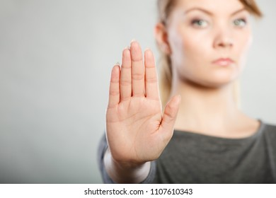 Prohibition symbol. Serious female shows stop sign talk to hand gesture. Angry full of negative emotions woman with hand palm stopping.