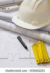 Project blueprints and engineer hardhat white color on drawings background. Housing project construction, architect site office concept.