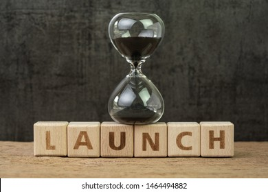 Project launch countdown, start business or start up company, hourglass or sandglass on wooden cube block with alphabet building the word Launch on wood table, dark black background.