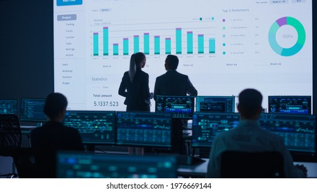 Project Leader, Chief Executive Discuss Data Shown on Big Display. Screens Show Infographics, Charts, Finance Analysis, Stock Market, Growth.Telecommunications Control Room with Working Professionals - Shutterstock ID 1976669144