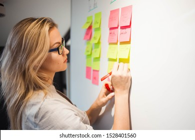 project management, agile methodology. young business woman in the office are working on a startup. Project manager plan work and stages of development of company, glue sticky leaves on Board