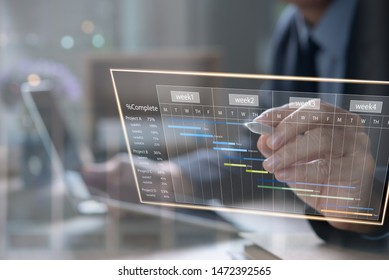 Project management. Project manager updating tasks, milestone progress planning with augmented reality Gantt chart scheduling on virtual screen. Businessman working on digital tablet, laptop computer