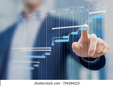 Project manager updating tasks and milestones progress planning with Gantt chart scheduling interface on a virtual screen - Shutterstock ID 734184223