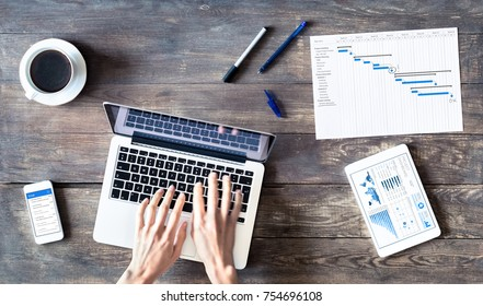 Project manager using laptop computer, printed Gantt chart planning with milestone and task schedule, smartphone and tablet computer with wireless internet, top view