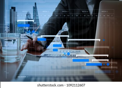 Project manager working and update tasks with milestones progress planning and Gantt chart scheduling diagram.business documents on office table with smart phone and digital tablet.