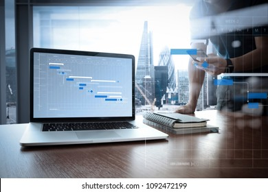 Project manager working and update tasks with milestones progress planning and Gantt chart scheduling diagram.designer hand working and smart phone and blank screen laptop on wooden desk in office.
