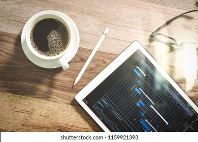 Project manager working and update tasks with milestones progress planning and Gantt chart scheduling virtual diagram.Coffee cup and Digital table dock smart keyboard,eyeglasses,stylus pen