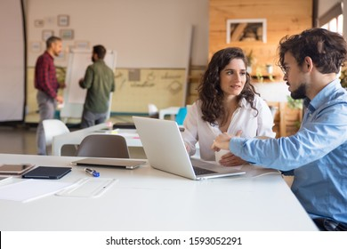 Project partners discussing ideas and using laptop together. Business colleagues in casual working together in contemporary office space. Corporate communication concept