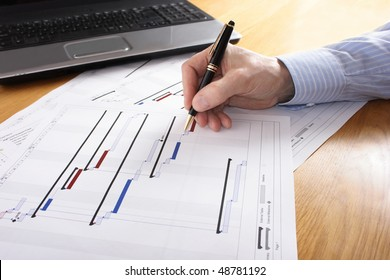 Project plan being annotated with hand and laptop in background