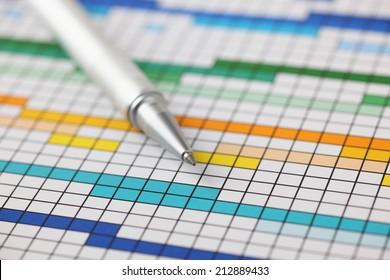 Project Plan (Gantt chart) and ballpoint pen on it. Close-up.