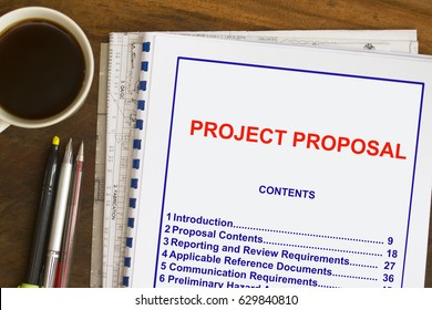 Project Proposal with coffee and documents - many uses in the oil and gas industry.