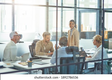 Project team at work. Group of multiracial business people sitting in board room in the modern office and discussing something while having a meeting
