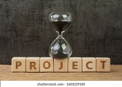 Project timeline countdown, launch business or start up company, hourglass or sandglass on wooden cube block with alphabet building the word Project on wood table, dark black background.