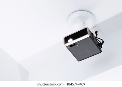 Projector mounted on a white ceiling