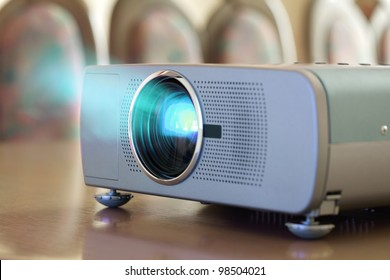 Projector on office table ready for presentation with chairs in background
