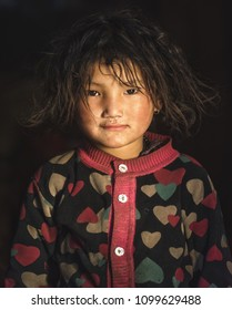 Prok village / Nepal - October 15 2017. Sweet little girl indoors with curly hair. Nepalese cute child girl in national clothes. Travel in Asia. Close up. Asian tribe in Himalayas. Portrait