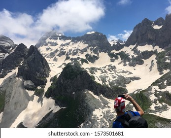 Prokletije, Montenegro: Mountain peaks in the distance and a hiker photographing them