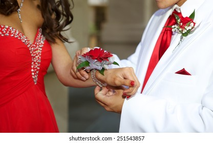 Prom Couple - a close up of the boy giving his date a red floral wrist corsage
