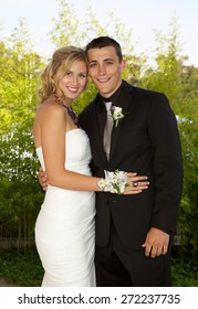 Prom couple outside posing for a photo.  The girl is blond and wearing a beautiful white dress and her date is wearing a black tuxedo with a black shirt.  They are smiling for the camera