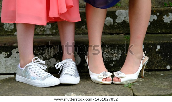 Prom girls in dresses standing with their legs at an angle showing off silver sparkly trainers and white high heels