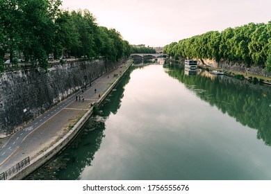 Promenade along the River Tiber in Rome, Italy, with people exercising, running and biking